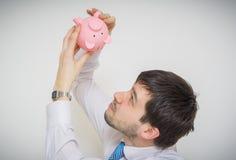 年轻商人在空的贪心金钱银行看 库存图片