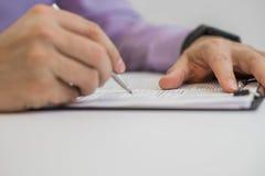 商人在笔记本写,当坐在书桌时 免版税库存图片