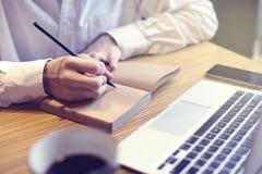 商人在笔记本的文字文本和看看在咖啡馆,公众共同工作的空间的被打开的膝上型计算机 有企业咖啡断裂 免版税库存图片
