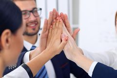 商人在签到协议或合同以后编组愉快的显示的配合和加入的手或者给五 库存图片