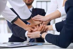 商人在签字以后编组商人小组愉快的显示的配合和加入的手或者给五 免版税库存照片