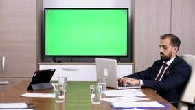 商人在绿色屏幕电视旁边的候选会议地点 股票录像