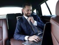 商人在膝上型计算机读信息,当坐在汽车时 免版税库存图片