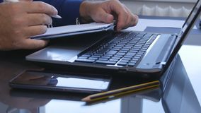 商人在膝上型计算机键盘的纸张文件写 库存照片