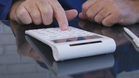 商人在计算使用加法器的办公室 免版税库存照片