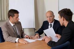 商人在证券交易经纪人行情室的会议 免版税库存图片