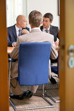 商人在证券交易经纪人行情室的会议 库存照片