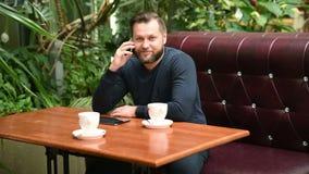 商人在谈话的咖啡馆坐电话和饮用的咖啡 咖啡馆的大忙人谈话与朋友 股票录像