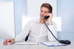商人在谈话的计算机前面坐电话 库存图片