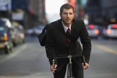 商人在都市街道上的骑马自行车 免版税库存图片