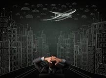 商人在都市风景图画前面坐chalkbo 免版税库存图片