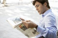 商人在长凳的读书报纸 免版税库存图片