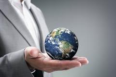 商人在他的手上的拿着世界 图库摄影