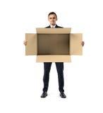 商人在他的手上的站立和拿着大开放空的轻的米黄纸板邮箱,隔绝在白色 免版税图库摄影