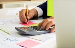 商人在frip c使用一个计算器并且写着笔记 免版税库存照片