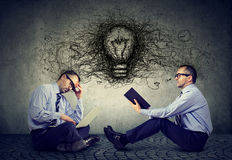 商人坐一个地板在办公室使用中间读与电灯泡和想法想法的膝上型计算机一本书 免版税图库摄影