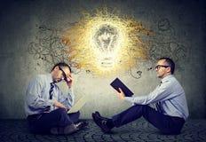 商人坐一个地板在办公室使用读与电灯泡想法想法的膝上型计算机一本书 免版税库存照片