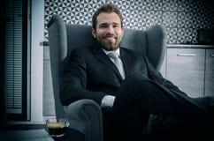 商人坐一把扶手椅子在家 免版税库存图片