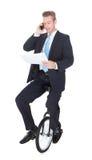 商人坐单轮脚踏车谈话在手机 免版税库存照片