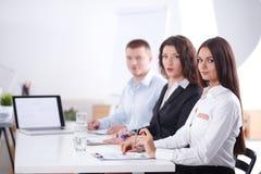 商人坐和谈论在业务会议上,在办公室 企业例证JPG人向量 免版税库存图片