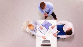商人坐和谈论在业务会议上,在办公室 库存图片