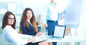 商人坐和谈论在业务会议上,在办公室 免版税图库摄影