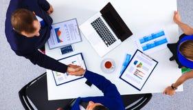 商人坐和谈论在业务会议上,在办公室 免版税库存照片