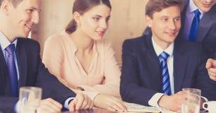 商人坐和谈论在业务会议上,在办公室 图库摄影