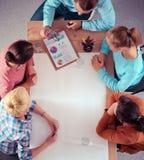 商人坐和谈论在会议上,在办公室 免版税图库摄影