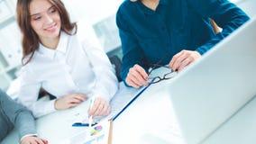 商人坐和谈论在办公室 免版税库存图片