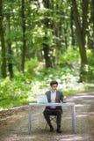 商人坐在办公桌工作的在便携式计算机和咖啡使用在绿色森林公园路的手机  Bu 免版税库存照片