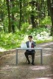 商人坐在办公桌工作的在便携式计算机和咖啡使用在绿色森林公园路的手机  Bu 库存图片