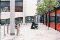 商人坐在寺庙酒吧,都伯林,爱尔兰的长凳 2015年 09 30 免版税库存照片