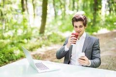 商人坐在有便携式计算机的办公桌的和咖啡在绿色森林公园使用手机 浓缩的事务 免版税库存照片