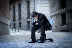 商人坐在街道上的办公室椅子在重音 免版税库存图片
