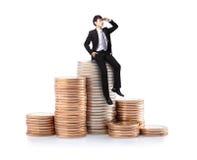 商人坐堆金钱硬币 免版税库存照片