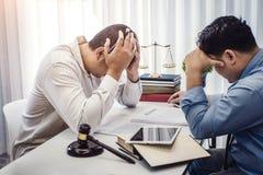 商人坐张力严肃为合同保险的问题与律师的在办公室 法官和法律,律师,法院法官 免版税图库摄影