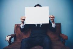 商人坐拿着空白的白色标志的沙发 库存照片