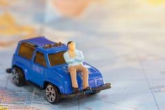 商人坐旅行的蓝色汽车环球 库存照片