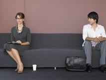 商人坐沙发在候诊室 免版税库存图片