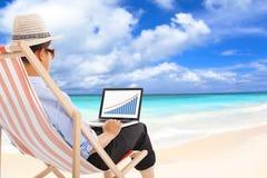 商人坐海滩睡椅和看起来储蓄财政 库存图片