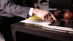 商人坐的办公桌签署法案他们,与个人计算机片剂比较 一个人和喷泉的特写镜头手 股票录像