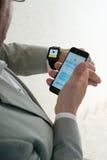 商人定购出租汽车使用他的苹果计算机手表 免版税库存图片