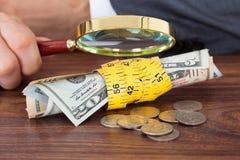 商人审查的钞票和硬币与放大镜 免版税库存照片