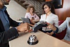 商人室的旅馆薪水有信用卡妇女在招待会的接待员注册的 免版税库存照片