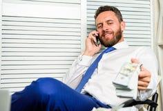 商人富有的有胡子的人坐有全部的办公室现金金钱 银行贷款或信用 得到获利少量分钟 班卓琵琶 免版税库存图片