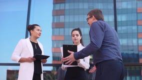 商人对好消息说给两个企业女孩,并且他们是愉快的 慢的行动 影视素材