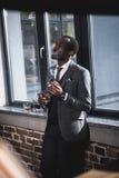 商人对负玻璃用威士忌酒和抽烟的雪茄户内 库存照片