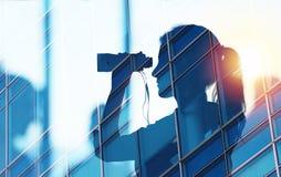商人寻找与双筒望远镜的新的工作机会 两次曝光 库存图片