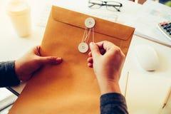 商人将打开包含busine的一个棕色信封 图库摄影